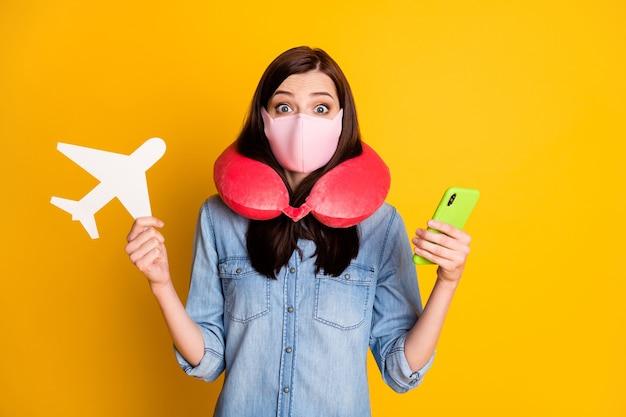 Fille étonnée en masque voyage cou doux confort oreiller tenir papier carte avion utiliser téléphone