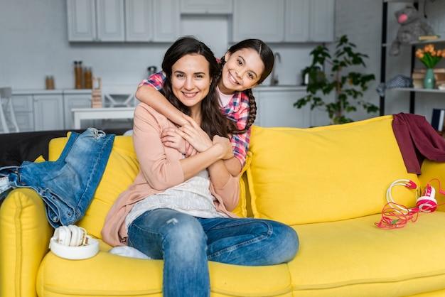 Fille étreignant sa mère sur le canapé