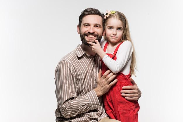 Fille étreignant son père sur un mur blanc