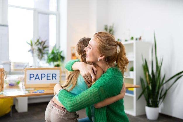 Fille étreinte. une enseignante aux cheveux blonds rayonnante se sentant heureuse tout en serrant une fille intelligente et travailleuse
