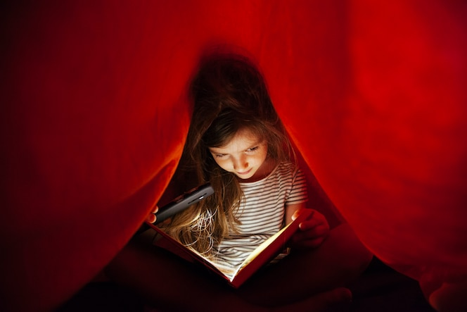fille étudiant un livre avec la lumière d'un téléphone