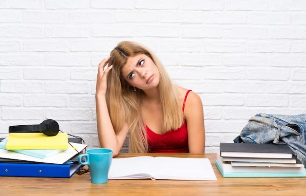 Fille étudiante adolescent à l'intérieur ayant des doutes tout en grattant la tête