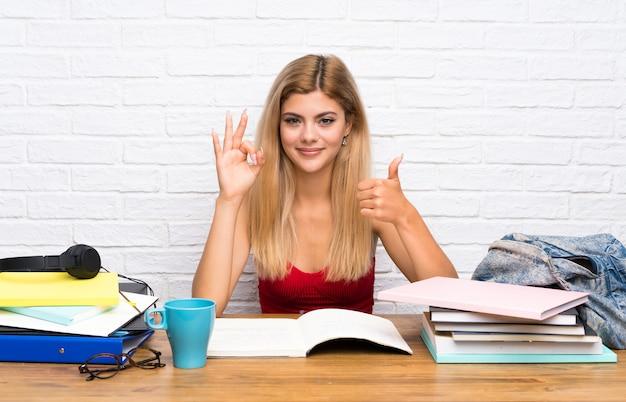 Fille étudiante adolescent à l'intérieur montrant le signe ok et le pouce vers le haut de geste