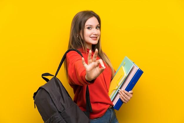 Fille étudiante adolescent sur jaune montrant un signe ok avec les doigts