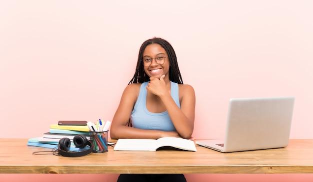 Fille étudiante adolescente afro-américaine avec de longs cheveux tressés sur son lieu de travail avec des lunettes et souriant
