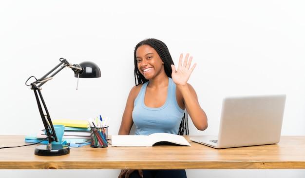 Fille étudiante adolescente afro-américaine avec de longs cheveux tressés sur son lieu de travail, saluant avec la main avec une expression heureuse