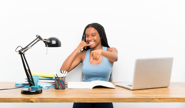Fille étudiante adolescente faisant un geste de téléphone et pointant devant