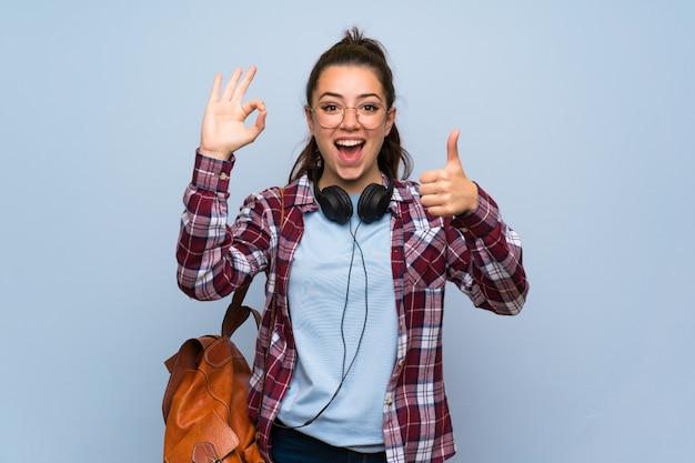 Fille étudiante adolescente sur mur bleu isolé, montrant le signe ok et le pouce vers le haut de geste