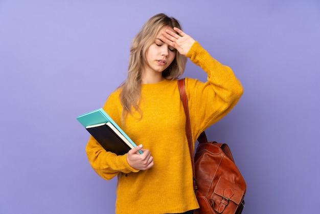 Fille étudiante adolescente sur mur violet avec une expression fatiguée et malade