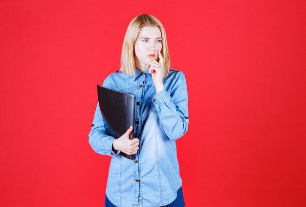 Fille étudiante adolescente tenant le dossier de document noir et pensant sur un mur rouge isolé