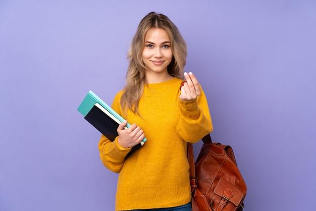 Fille étudiante adolescente sur violet faisant le geste de l'argent