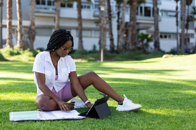 Fille étudiante afro assise sur l'herbe du campus avec une tablette numérique.