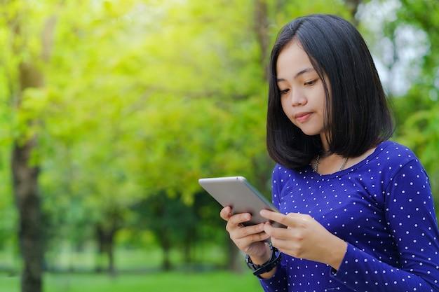 Fille étudiante asiatique en utilisant une tablette numérique dans le parc dans une journée d'été ensoleillée