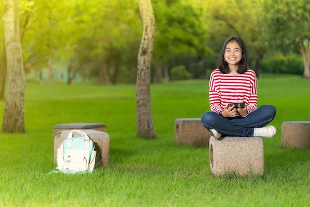 Fille étudiante asiatique en utilisant une tablette numérique dans le parc de l'école dans une journée d'été ensoleillée