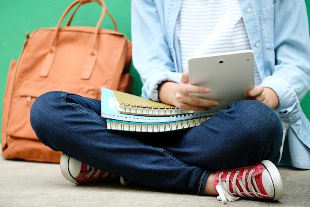Fille étudiante assise et à l'aide de tablette numérique, éducation en ligne, concept d'apprentissage adulte