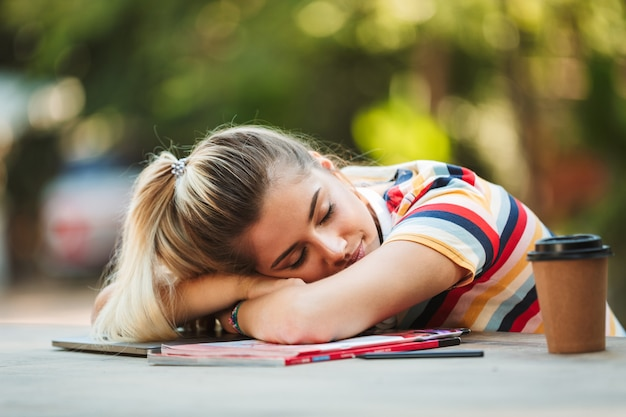 Fille étudiante assise dans le parc dormir