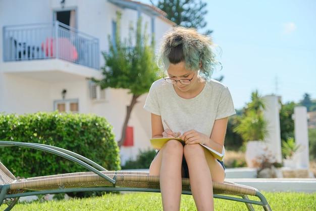 Fille étudiante assise en plein air, écrit dans le cahier d'école