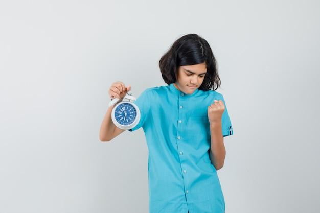 Fille étudiante en chemise bleue tenant horloge tout en montrant le geste du gagnant