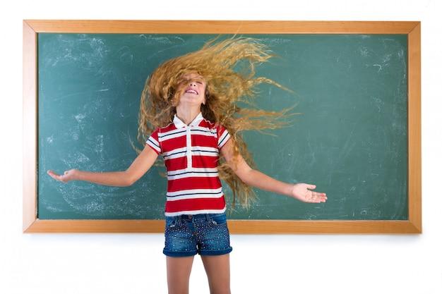 Fille étudiante drôle retournant les cheveux longs à l'école