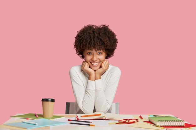 Fille étudiante heureuse posant au bureau contre le mur rose