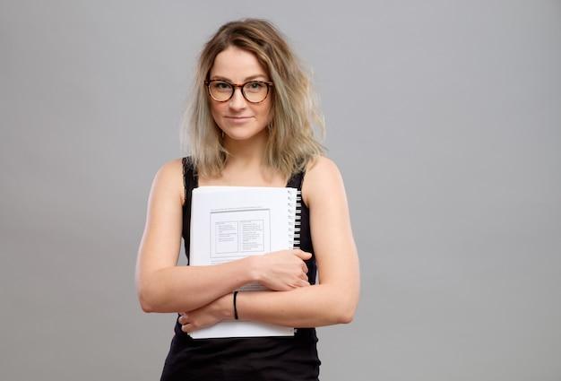 Fille étudiante avec des lunettes tenant un livre