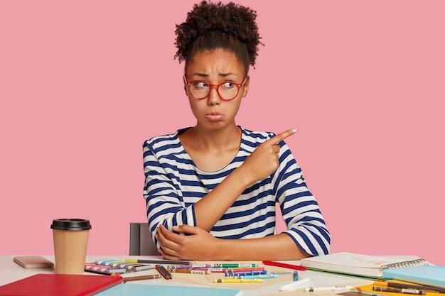 Fille étudiante mécontente posant au bureau contre le mur rose