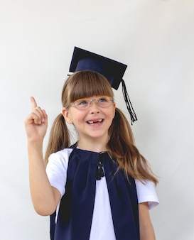 La fille étudiante mignonne intelligente sur fond gris