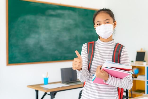 Fille étudiante primaire pouce vers le haut et portant des masques