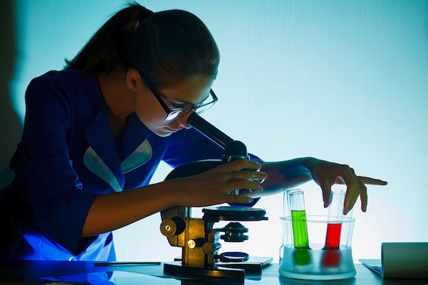 Fille étudiante à la recherche dans un microscope, concept de laboratoire scientifique.