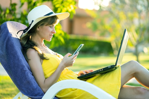 Fille étudiante en robe d'été jaune reposant sur la pelouse verte dans le parc d'été étudiant sur ordinateur portable textos sur téléphone portable
