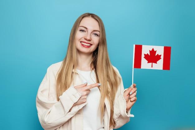 Fille étudiante souriant et pointant un doigt sur le petit drapeau du canada
