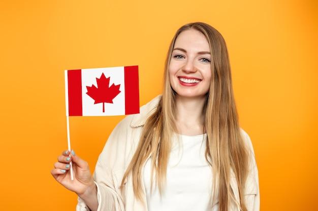 Fille étudiante souriant et tenant un petit drapeau canada