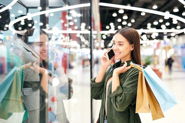 Fille étudiante souriante avec des sacs en papier debout à la vitrine et regardant la robe tout en demandant conseil à un ami par téléphone