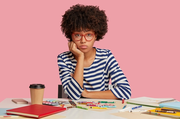 Fille étudiante triste posant au bureau contre le mur rose