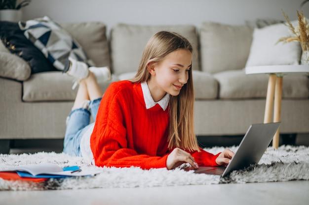 Fille étudie à la maison sur l'ordinateur