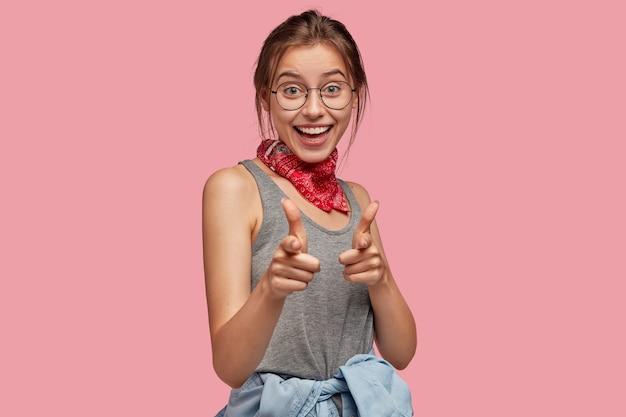Fille européenne assez positive à lunettes rondes, bandana rouge, t-shirt gris