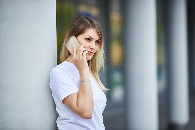 Fille européenne aux cheveux raides, parler au téléphone.