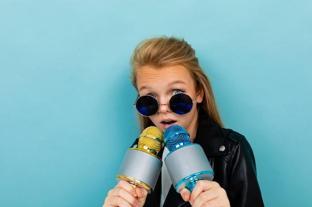 Fille européenne à lunettes de soleil avec deux microphones à la main sur bleu clair