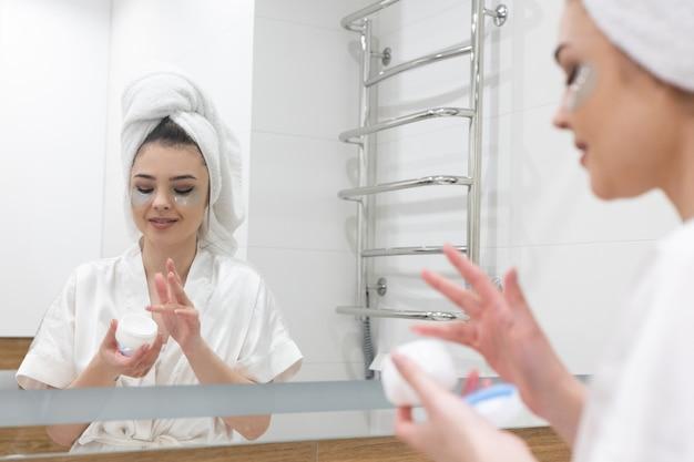 Une fille européenne prend de la crème dans un récipient cosmétique. belle jeune femme avec un cache-œil sur le visage et une serviette de bain enveloppée sur la tête. concept de soins de la peau du visage. intérieur de salle de bains dans l'appartement moderne