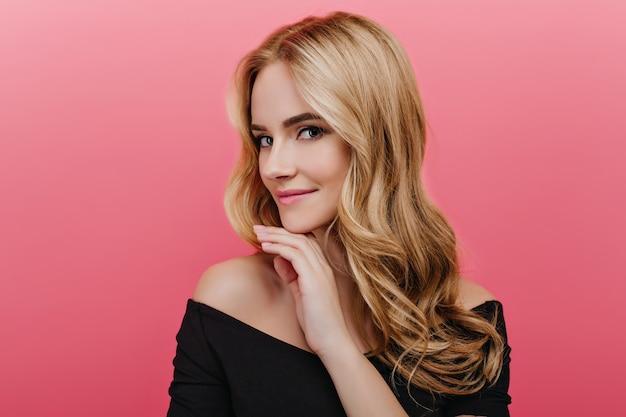 Fille européenne romantique aux yeux bleus posant avec l'expression du visage intéressé. winsome jeune femme bouclée en noir debout isolé sur un mur rose.