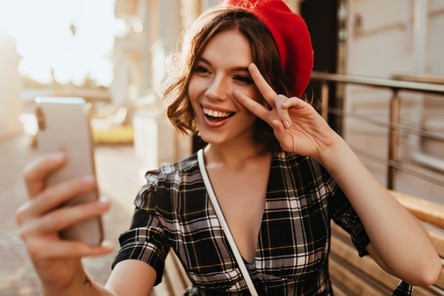 Fille excitée en béret rouge à l'aide de smartphone pour selfie dans la rue. jolie dame caucasienne prenant une photo d'elle-même et regardant l'écran du téléphone.
