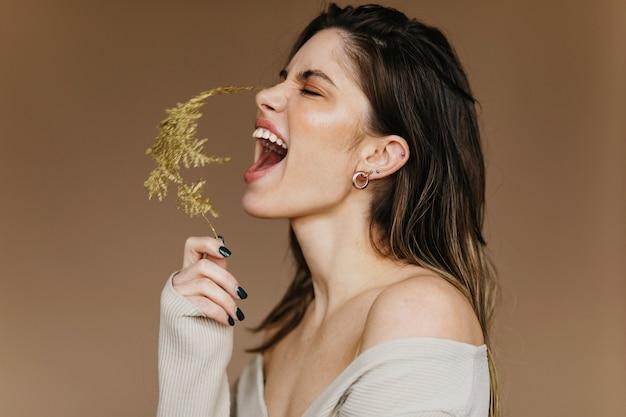 Fille excitée en boucles d'oreilles posant avec fleur. jeune femme brune inspirée en riant pendant le tournage.