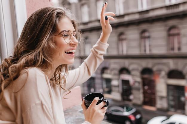 Fille excitée avec une coiffure frisée agitant la main à quelqu'un, regardant la fenêtre
