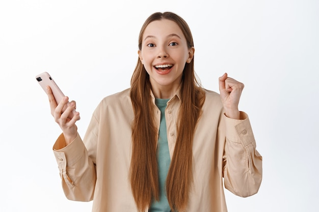 Fille excitée gagnant en ligne, sautant du bonheur avec un smartphone, célébrant la victoire, recevant un message avec de bonnes nouvelles, souriant et disant oui, mur blanc
