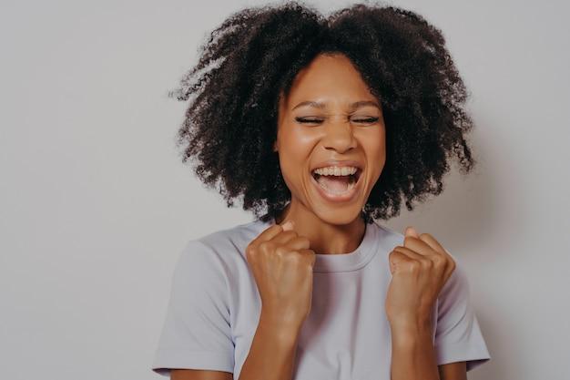 Une fille excitée et joyeuse à la peau sombre serre les poings tout en fermant les yeux s'exclame de victoire ou prête à gagner, une femme excitée vêtue de vêtements décontractés crie oui, isolée sur blanc