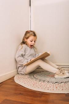 Fille excitée lisant un livre sur le sol