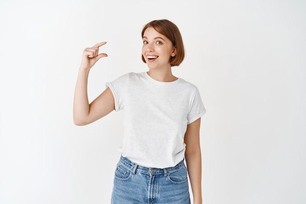 Fille excitée montrant une petite taille, une petite chose et souriante, faisant une petite forme avec les doigts, debout contre un mur blanc