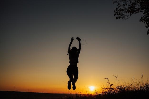 Fille excitée sautant au coucher du soleil.