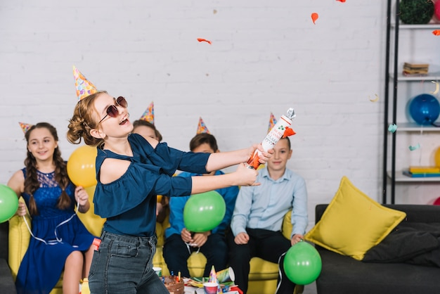 Fille excitée souffle le popper de confettis à la fête d'anniversaire