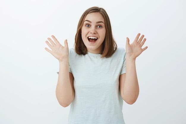 Fille excitée et surprise de voir un ami soulever de façon inattendue les paumes près de l'épaule haletant et souriant joyeusement de stupéfaction et d'émotions positives debout dans un t-shirt à la mode sur un mur gris